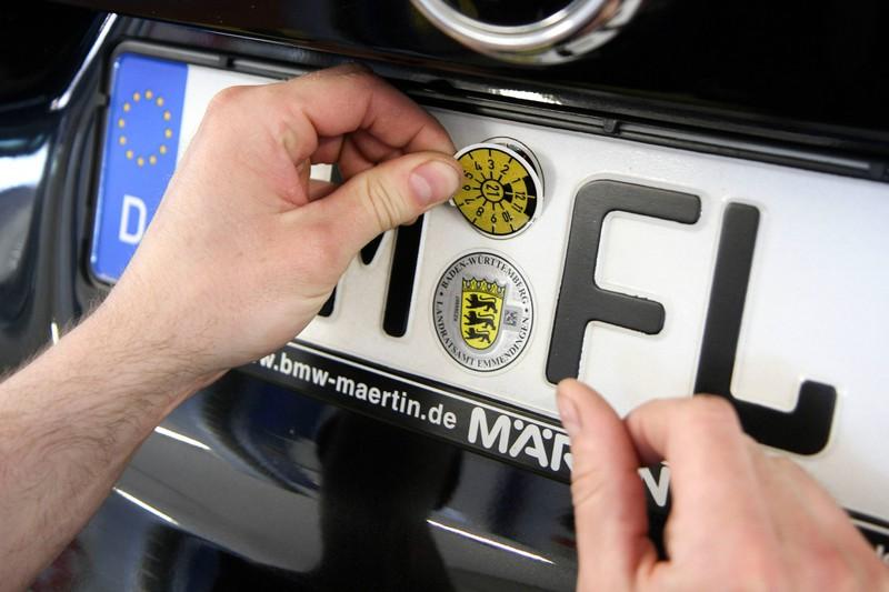 Eine neue TÜV-Plakette wird am Nummernschild angebracht