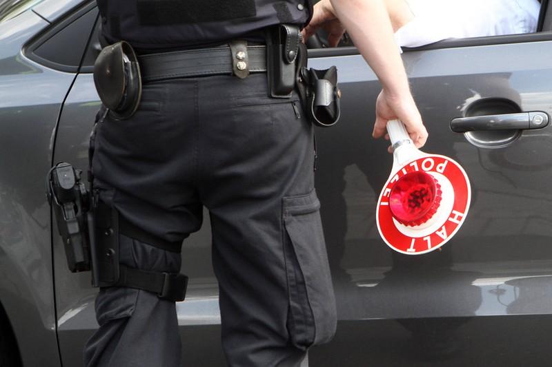 Ein Polizist tritt während einer Verkehrskontrolle an das Auto eines Fahrers heran.