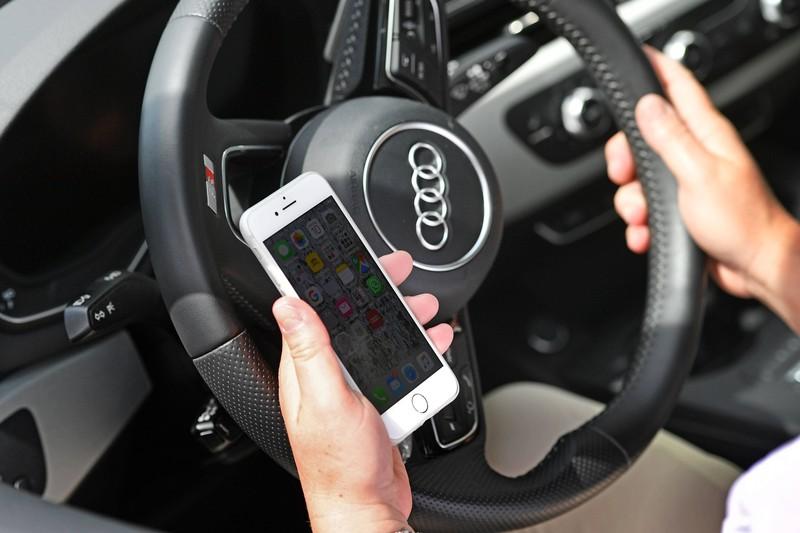 Zu sehen ist ein Autofahrer, der am Steuer des Fahrzeugs sitzt und auf ein Handy schaut.