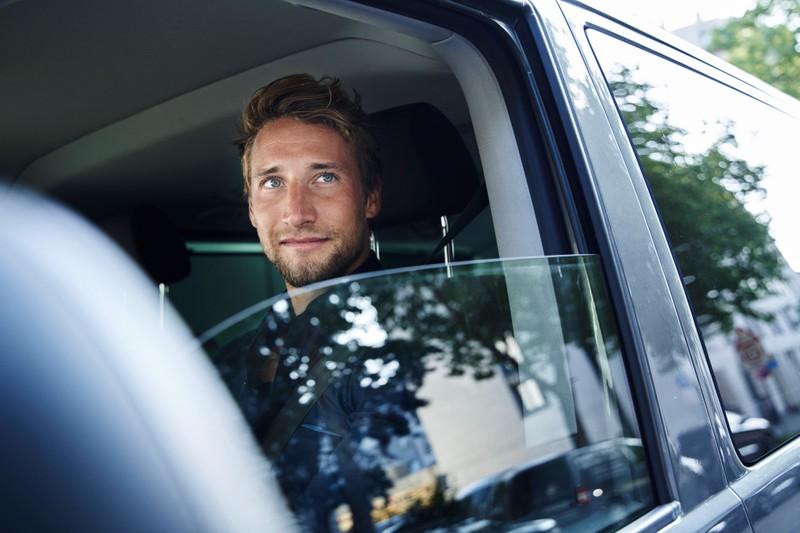 Zu sehen ist ein junger Mann, der in einem Auto sitzt und bei einer Verkehrskontrolle aus dem Fenster schaut.