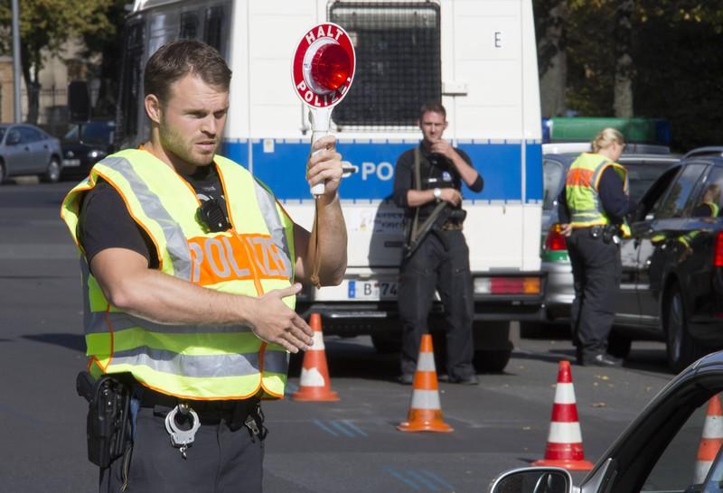 Zu sehen ist ein Polizist, der einen Autofahrer zur Verkehrskontrolle stoppt.
