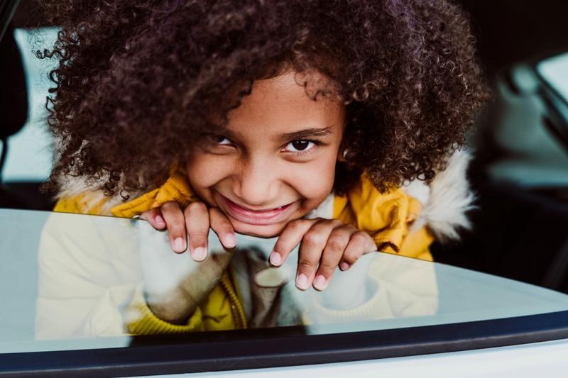 Ein Kind schaut vom Beifahrersitz eines Autos aus dem Fenster heraus.