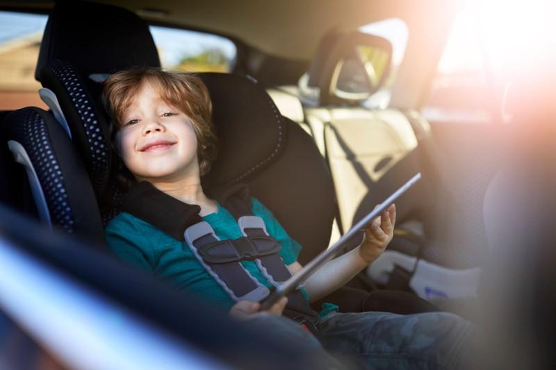 Zu sehen ist ein Junge, der auf dem Rücksitz eines Autos mitfährt und ein Tablet in der Hand hält.