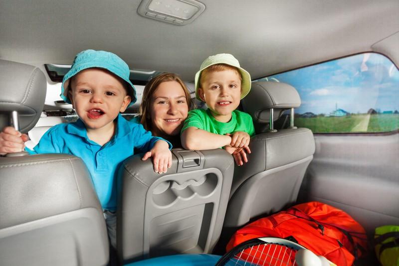 Zu sehen sind eine Mutter und zwei Kinder, sowie das Gepäck im Kofferraum eines Autos.