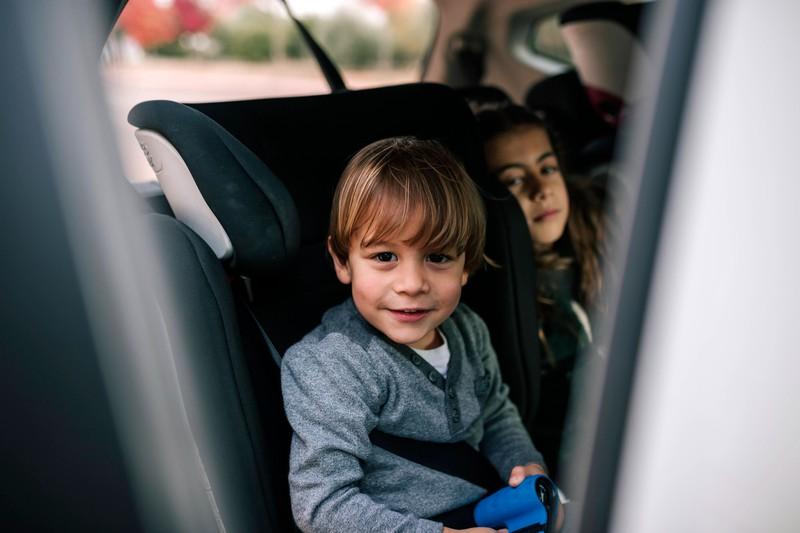 Zu sehen sind zwei Kinder, die aus einer offenen Autotür hinausschauen.