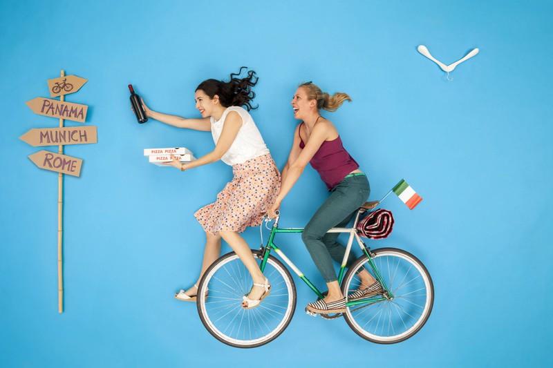 Frauen auf Fahrrad mit Weinflasche
