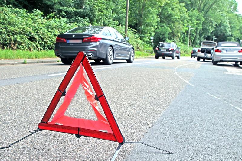 Dieses Bild zeigt ein Warndreieck, das auf einen Autounfall hinweist.