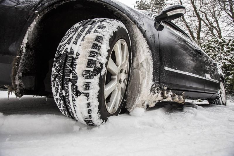 PKW fährt mit Winterreifen durch den Schnee