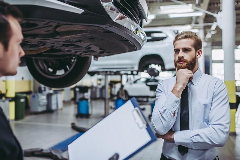 Ein Mann steht in einer Auto-Werkstatt, die ihn potentiell abzocken könnte