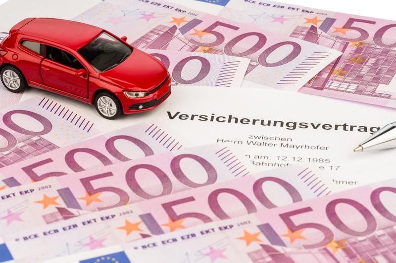 Ein Auto, das auf einem Versicherungsvertrag steht, der teuer oder günstig ausfallen kann