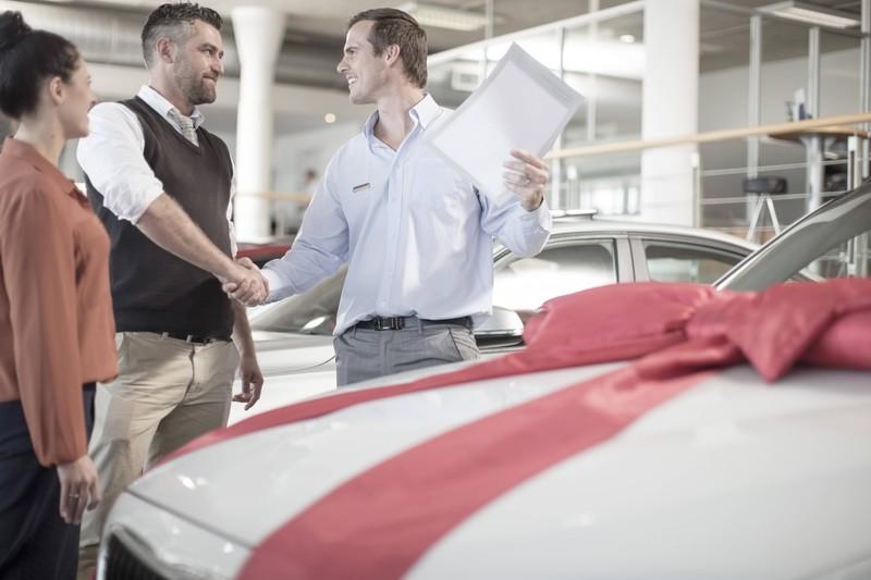 Ein Mann kauft seinen neuen Wagen direkt beim Händler.
