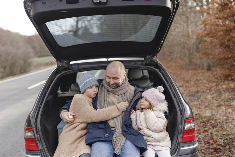Ein Vater sitzt mit seinen Kindern in seinem großen Kofferraum.