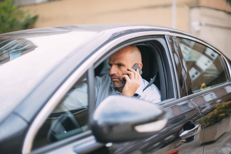 Mann telefoniert mit Handy am Steuer, aber das ist nicht erlaubt