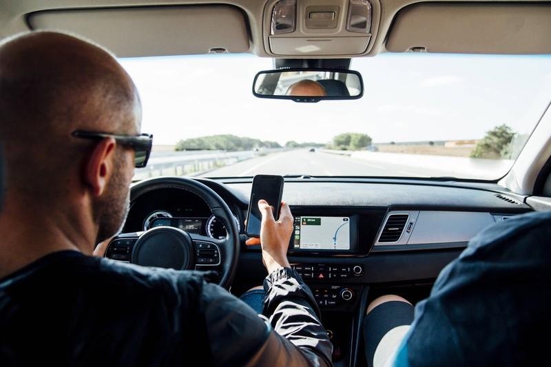 Was ist beim Autofahren verboten? Mann sitze am Steuer und schaut auf sein Handy