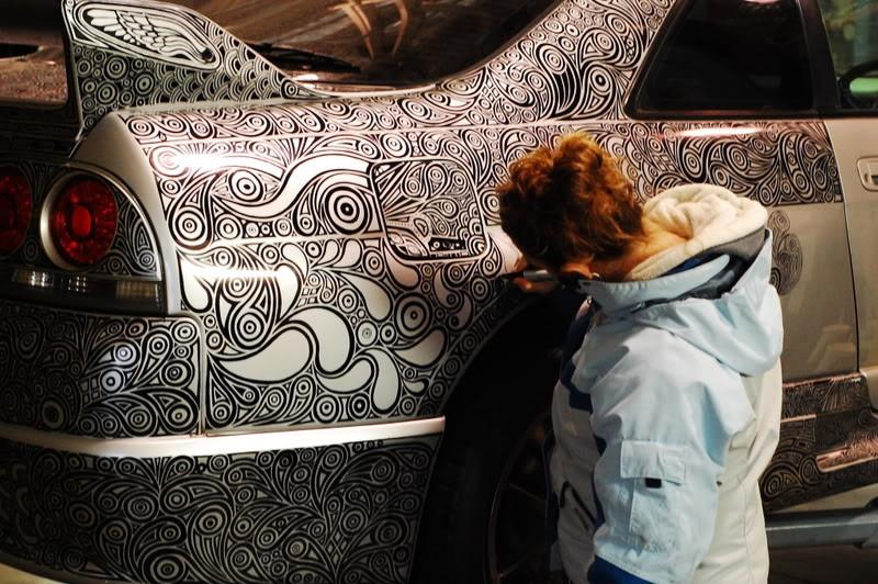 Die Frau bemalt das Auto mit einem Fasermaler, sodass es zu einem Kunstwerk heranwächst.