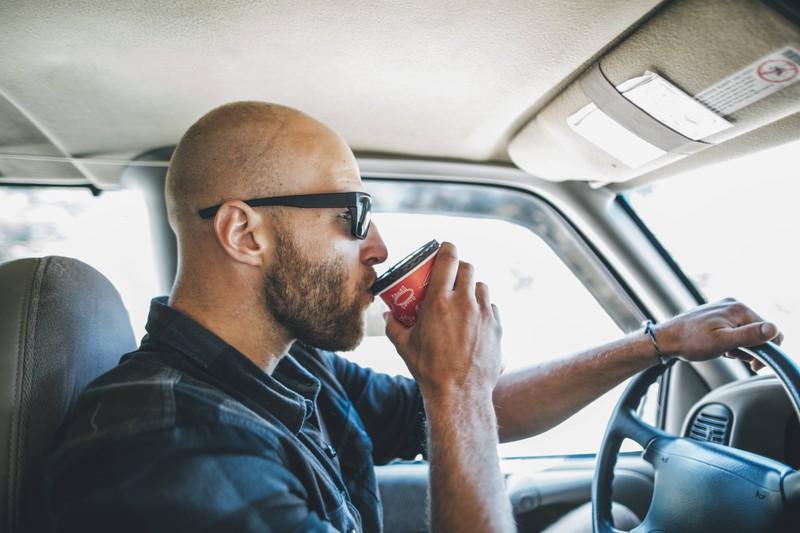 Das Bild illustriert einen Mann, der im Auto etwas trinkt, was bei Hitze wichtig ist