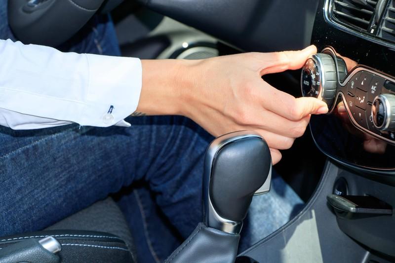 Ein Bild eines Fahrers, der im Auto die Klimaanlage zu hoch einstellt, was ein Fehler bei Hitze ist