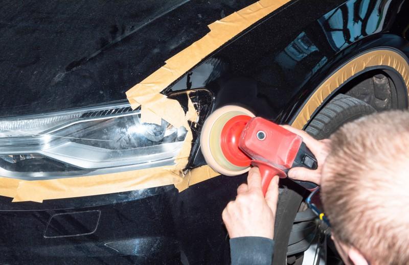 Ein Foto von einem Mann, der den Lack des Autos poliert, was bei Hitze schädlich sein kann