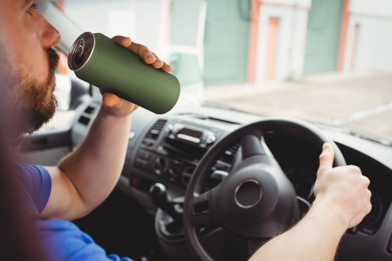 Es ist ein Mann zu sehen, der im Auto versucht nicht das Falsche zu trinken
