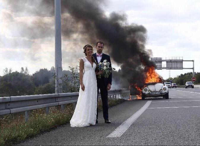 Hochzeitspaar steht vor brennenden Auto
