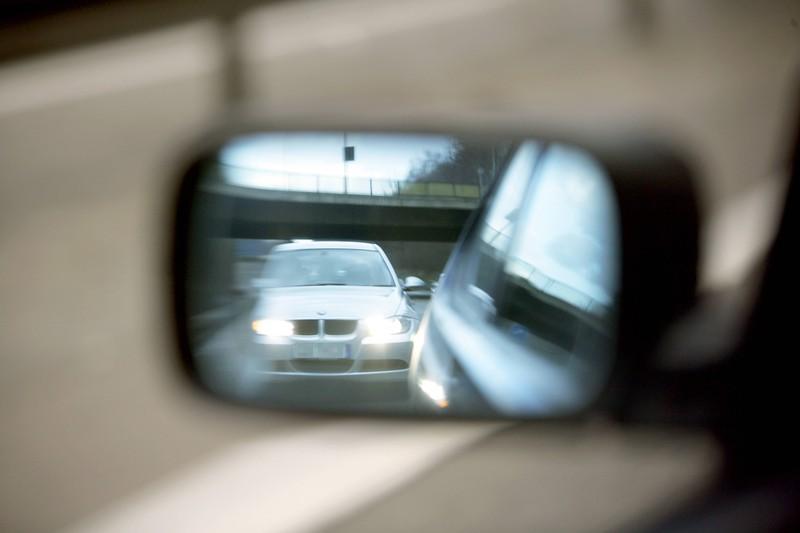 Ein Autofahrer macht Lichthupe hinter einem anderen Wagen