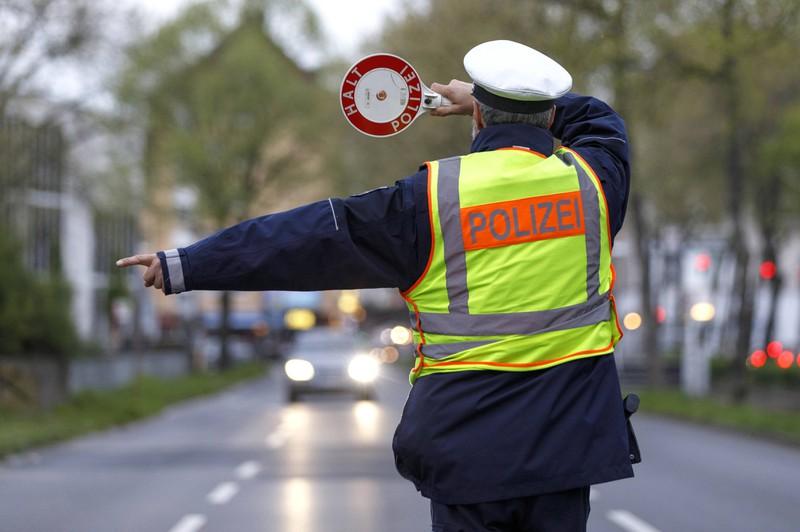 Der Polizist winkt Leute heraus, die ein Handy am Steuer nutzen, was der Blitzer erkannt hat.