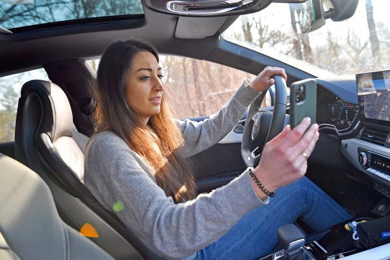 Die Frau schaut während der Autofahrt auf ihr Handy.